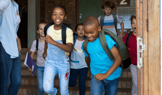 Children playfully running out of a school