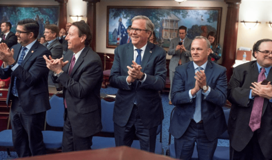 Former Florida Gov. Jeb Bush, center, applauds on the floor of the Florida House of Representatives after the passage of the Family Empowerment Scholarship program.