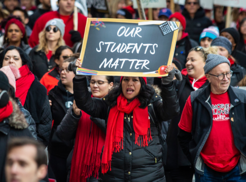 """Thousands of striking Chicago Teachers Union and their supporters march around City Hall in October 2019. One person in front holds up a sign that reads, """"Our Students Matter."""""""
