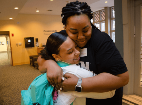 "Crystalle Green, the Communities in Schools of Mid-America site coordinator for Cross- roads Preparatory Academy in Kansas City, Missouri, hugs a student headed to class during a ""Motivational Monday"" event."