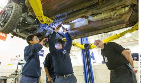 Worcester Technical High School teacher Louis Desy, right, watches as Zaire Peart, left, holds a flashlight for Kyle Dipilato, who is disassembling a car donated by a local salvage company.