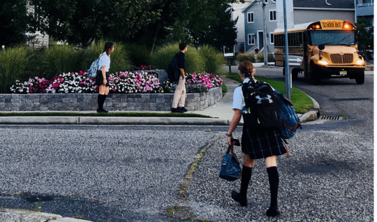 Students wearing school uniforms wait for a bus.