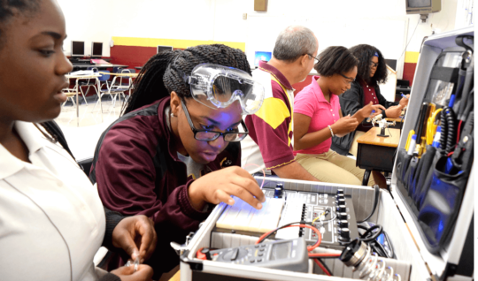 "Training for high-tech: In Chattanooga, Tennessee, Tyner Academy students (from left) Jada Beckett and Takayla Sanford work on building circuits, while ""mechatronics"" teacher Bryan Robinson instructs Brookeana Willams and Noemy Marberry about soldering."