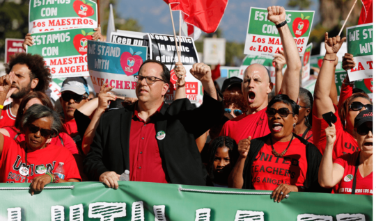 The president of United Teachers Los Angeles, Alex Caputo-Pearl, center, joins unionized teachers at a rally in the city in 2018.