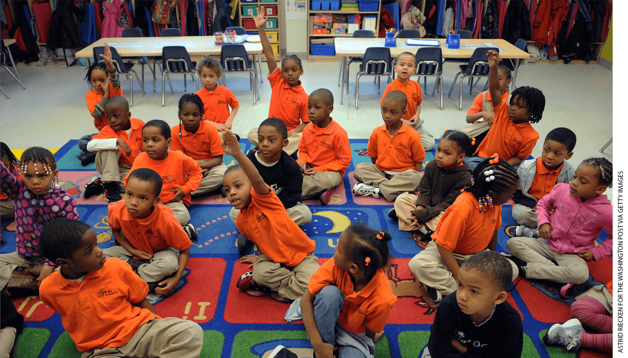 A classroom with children sitting on the floor, raising their hands