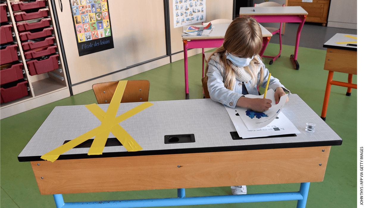 A student at the Sainte-Croix elementary school works as half of her writing desk is marked with a tape to ensure that safe distance is kepton May 15, 2020, in Hannut, Belgium.