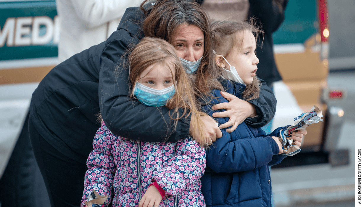"""A mother wearing a mask holds her two children outside of NYU Langone Health hospital during the nightly """"Clap Because We Care"""" cheer for medical staff and essential workers."""