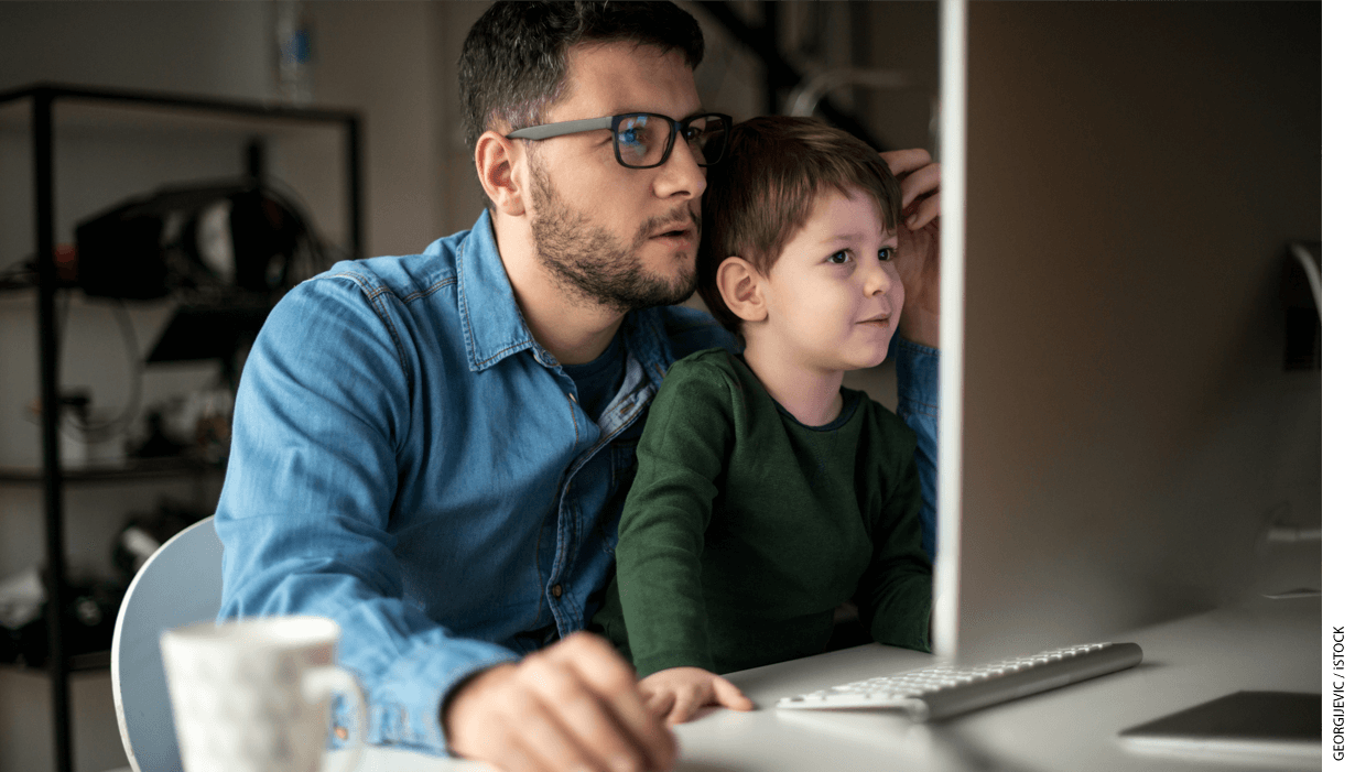 A man and boy looking at a computer monitor together.