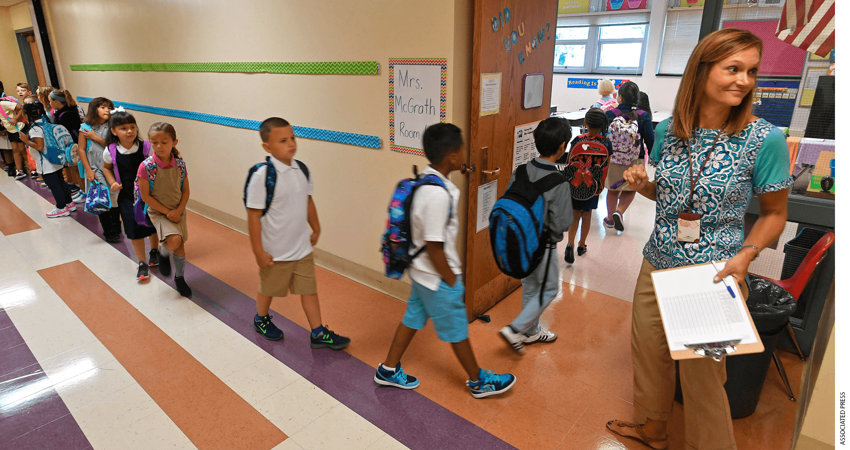 Teacher holding clipboard welcomes students as they enter classroom