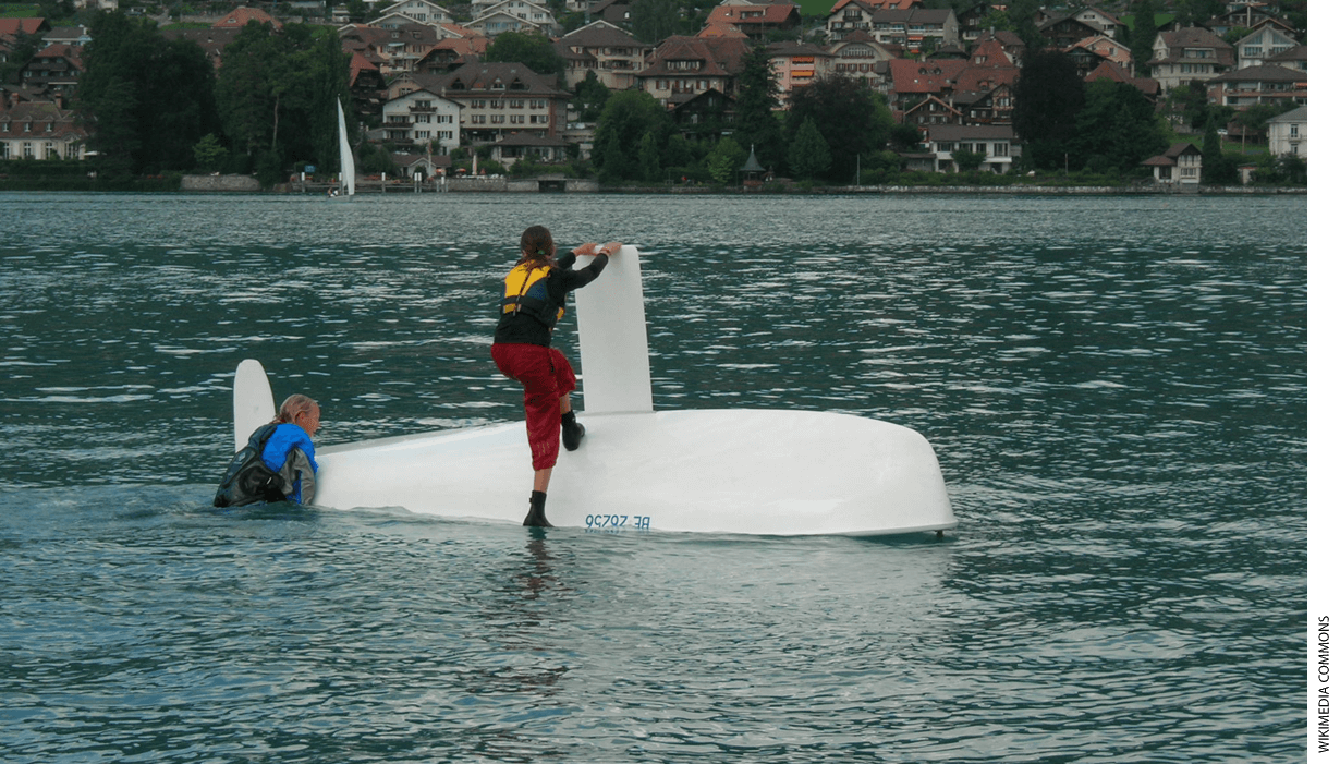 Two sailors on a turtled sailboat