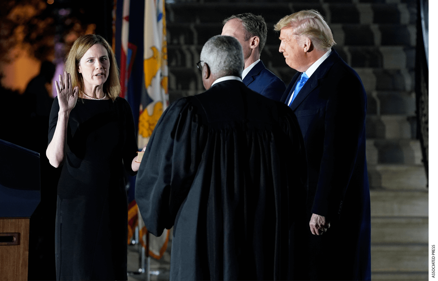 President Donald Trump watches as Supreme Court Justice Clarence Thomas administers the Constitutional Oath to Amy Coney Barrett on the South Lawn of the White House in Washington, Monday, Oct. 26, 2020, after Barrett was confirmed by the Senate earlier in the evening.