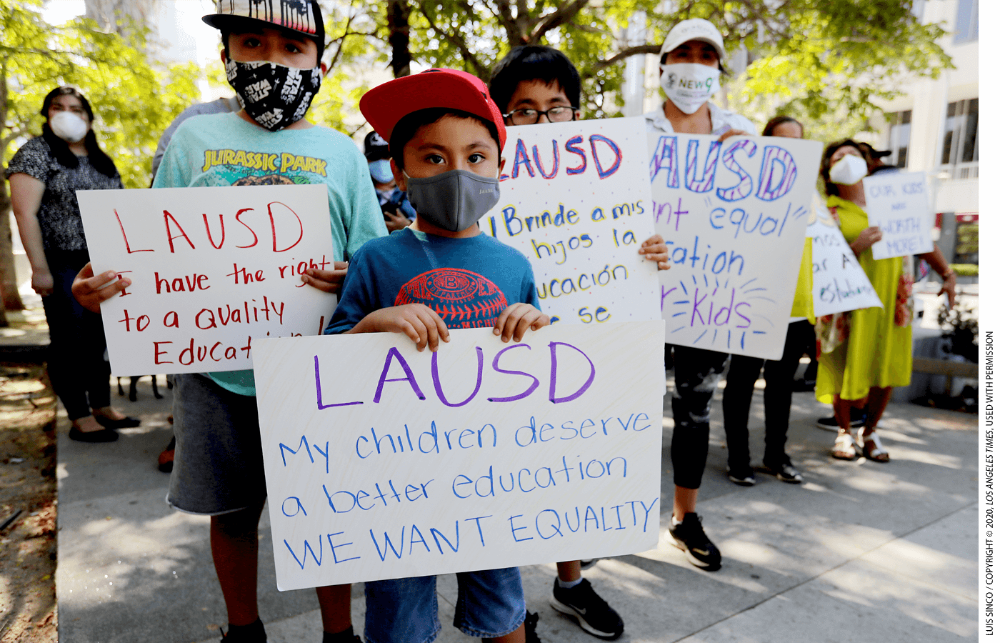 "Student holds a sign outside a news conference that reads ""LAUSD: My children deserve a better education WE WANT EQUALITY"""