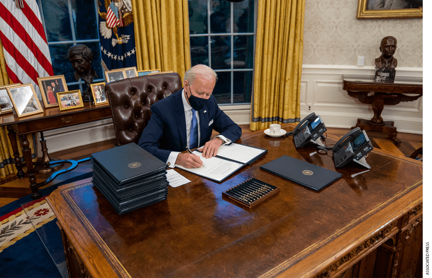 United States President Joe Biden signs executive order on Covid-19 during his first minutes in the Oval Office, Wednesday, Jan. 20, 2021.