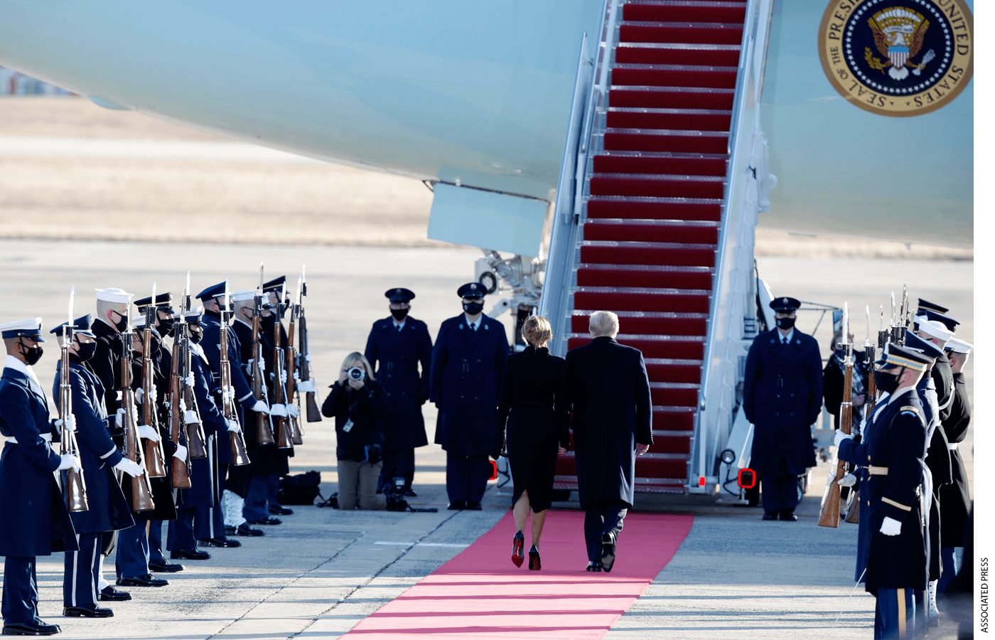 President Donald Trump and first lady Melania Trump are greeted by a military honor guard as they board Air Force One at Andrews Air Force Base, Wednesday, Jan. 20, 2021.