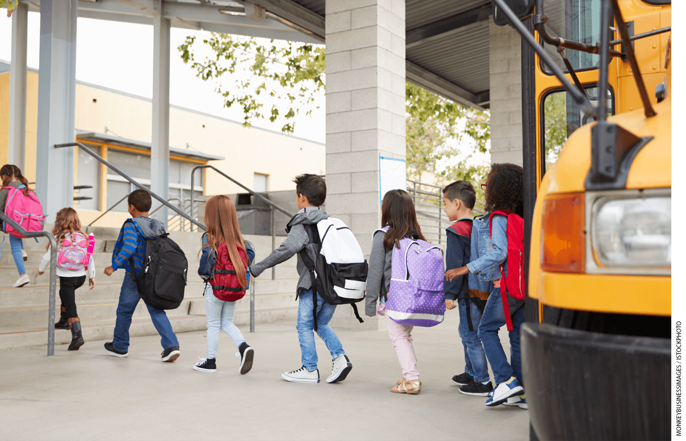 Students file off a bus and walk into a school