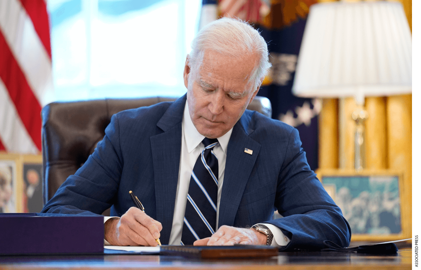 President Joe Biden signs the American Rescue Plan, a coronavirus relief package, in the Oval Office of the White House, Thursday, March 11, 2021.