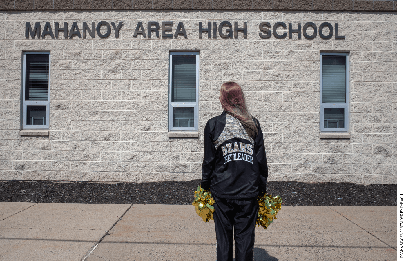 Cheerleader stands in front of Mahanoy Area High School