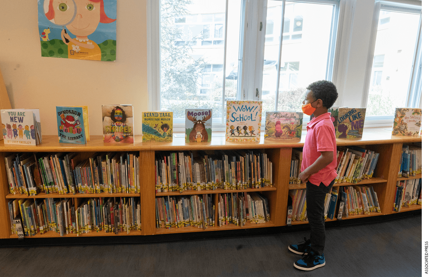 A first grader picks out a book he would like to check out at the Post Road Elementary School Library, Thursday, Oct. 1, 2020, in White Plains, N.Y.
