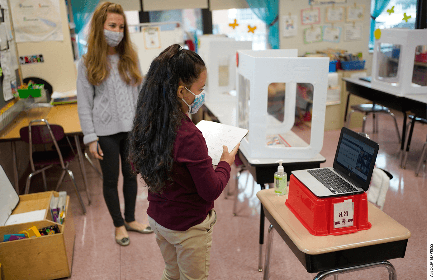 Third grader Madison Cortes, right, reads off math problems to classmates on zoom while teacher Maria Mirkovic looks on at Christa McAuliffe School in Jersey City, N.J., Thursday, April 29, 2021.