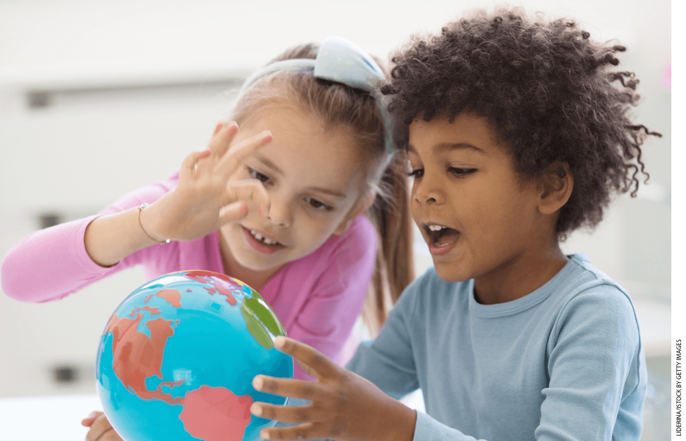 Two students in a classroom looking at a globe