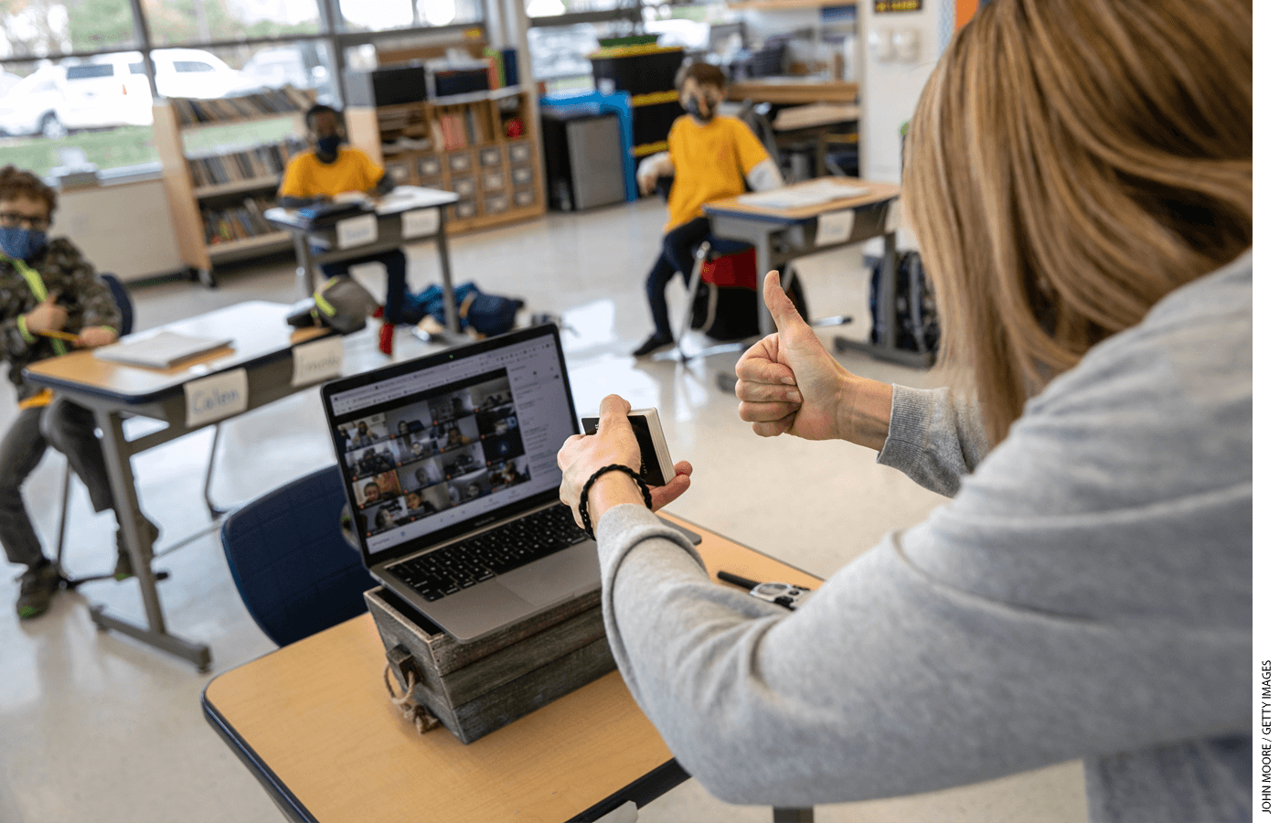 Third-grade teacher Cara Denison manages students in person and remotely, simultaneously, at Rogers International School in Stamford, Connecticut.