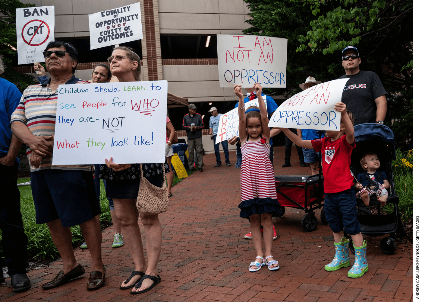 """People hold up signs during a rally against """"critical race theory"""" being taught in schools. The rally was at the Loudoun County Government center in Leesburg, Virginia on June 12, 2021."""