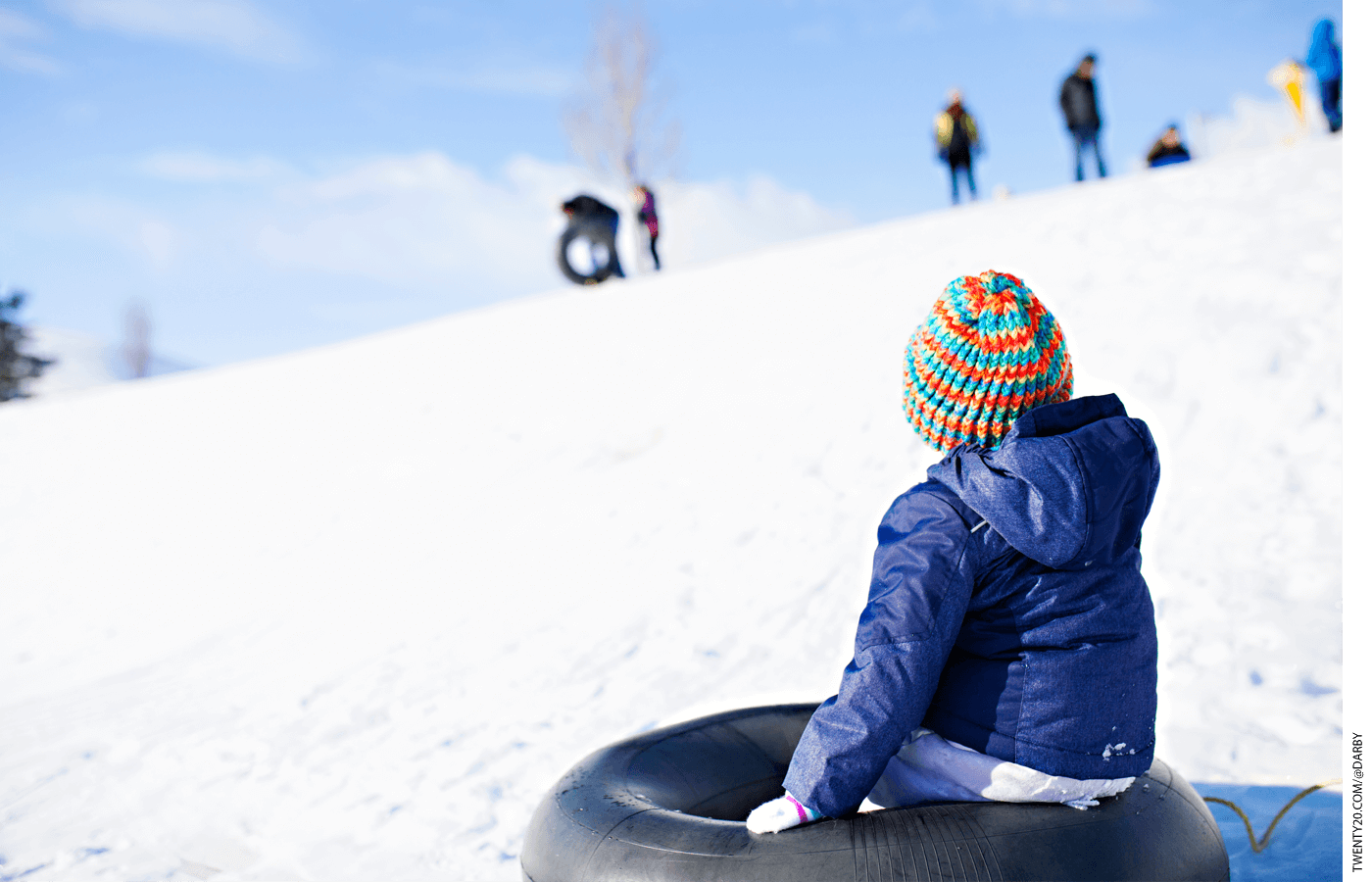 Kid sitting on a tube in the snow