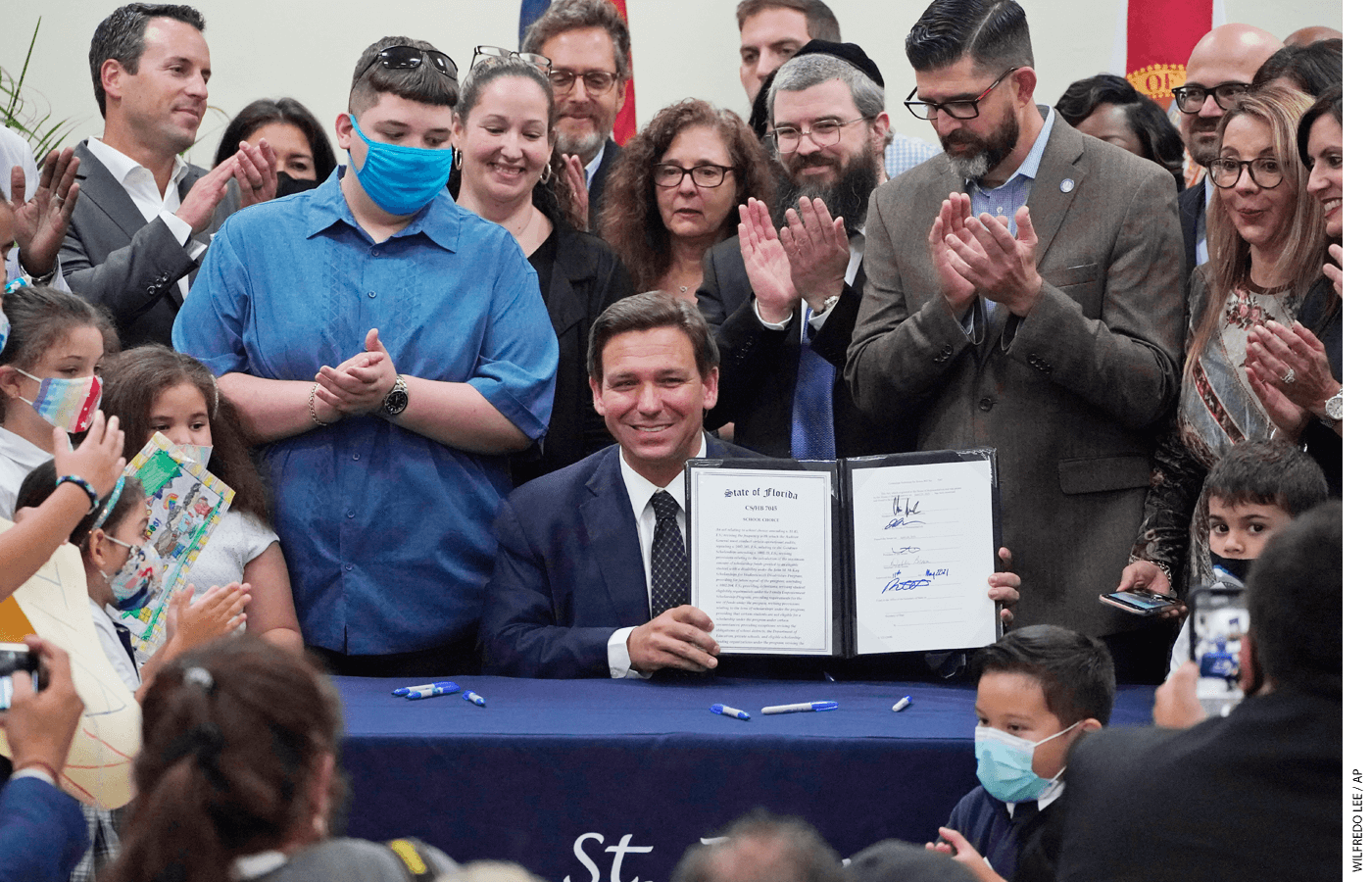 Florida Gov. Ron DeSantis, seated, celebrates after signing a bill that expands eligibility for state scholarships to fund private-school tuition.