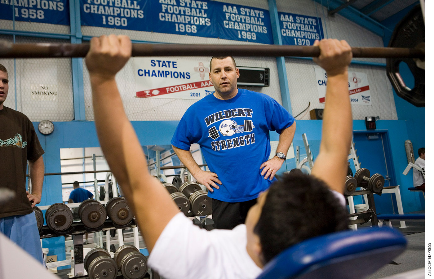 A high-school football player lifts weights while his coach watches.