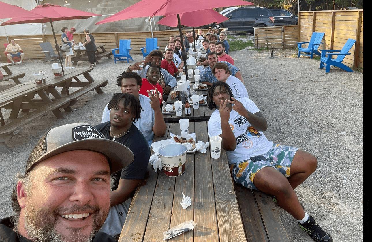 Jordan Wright, shown front bottom left, owner of Wright's Barbecue, a popular Arkansas restaurant, is sponsoring the entire offensive line of the University of Arkansas Razorbacks men's football team.