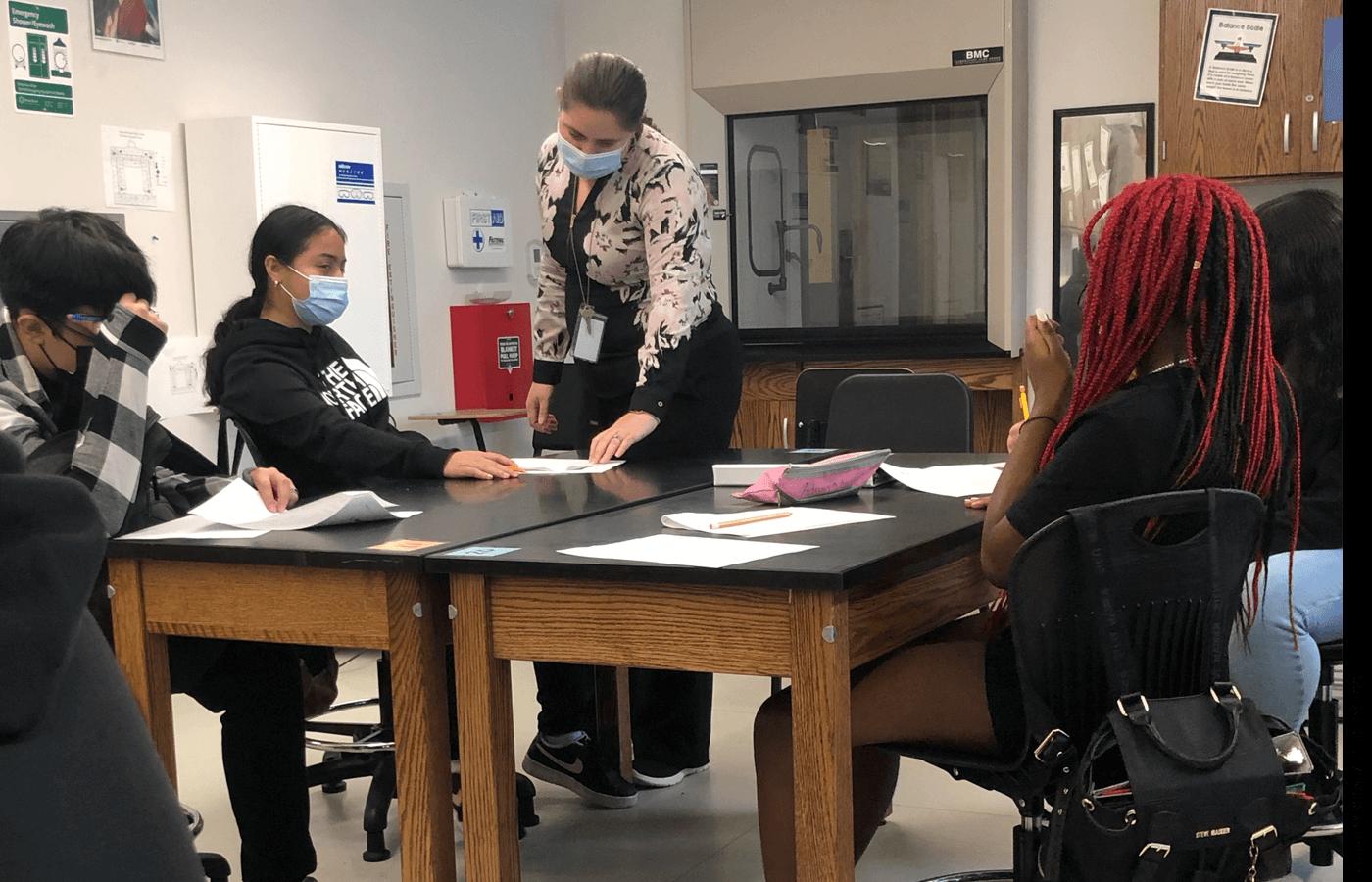 Begaeta Ahmic, a math teacher at Roosevelt High School, helps students with their work.