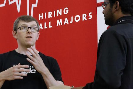 In this Sept. 25, 2014 file photo, Jacob Robinson, left, of Epic, an electronic health record software company, speaks with students attending The Foot in the Door Career Fair at the University of Illinois Springfield in Springfield, Ill. The Labor Department issued its November report on job openings and labor turnover on Tuesday, Jan. 13, 2015. (AP Photo/Seth Perlman, File)