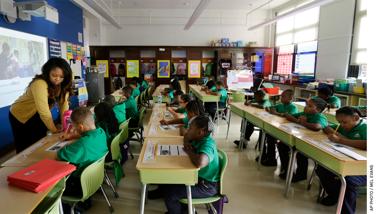 Teacher Shanel Sommers looks over the work of one of her third-graders at KIPP Thrive Academy in Newark, N.J.