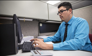 This photo shows a boy working one day per week. Didier Garcia, age 18, is a senior at a Cristo Rey School, the St. Martin College Prep in Waukegan, Illinois.  He labors on inputting invoice information at Stepan Chemical in Northbrook (Tuesday, Sept. 15, 2015).  One notes his professional appearance, shirt and tie, and attention, learned by working and earning most of his own school tuition. Note also his opportunity to attend a Catholic school even though he come's from a poor family.