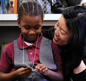 Rhee visits with first grader Sasha Simpson.