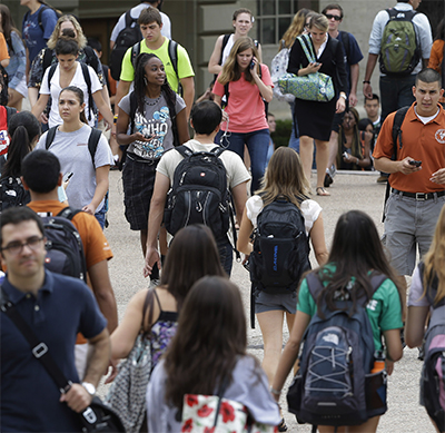 Students walk through the campus of the University of Texas at Austin. (Photo by Eric Gay/Corbis Images)