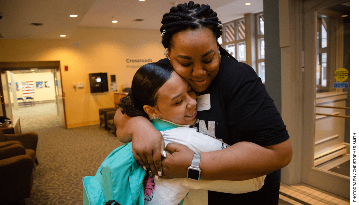 """Crystalle Green, the Communities in Schools of Mid-America site coordinator for Cross- roads Preparatory Academy in Kansas City, Missouri, hugs a student headed to class during a """"Motivational Monday"""" event."""