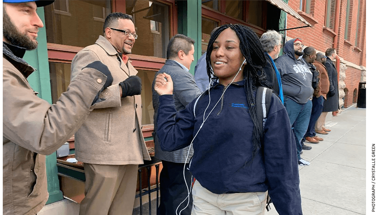 Green recruited a group of young professional men from the community to greet students outside on the sidewalk as they arrive for the day. The middle- and and high-school students walk a gauntlet of fist bumps and high-fives on the way into the school.