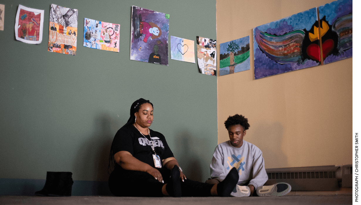 Green does a meditation exercise with student Jayshon Anderson in a room featuring student-created art.