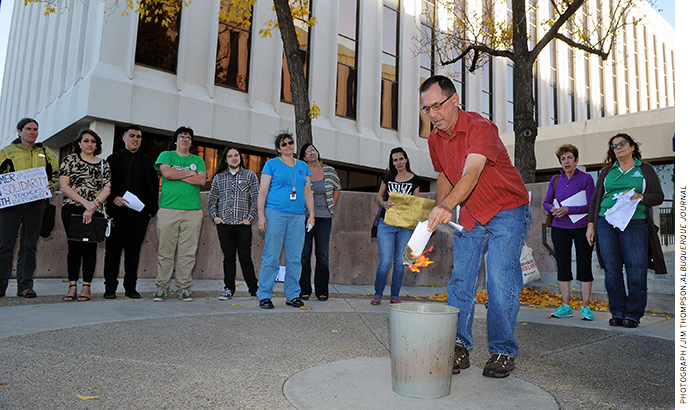 An elementary school teacher burns his evaluation during a protest in front of the Albuquerque Public Schools headquarters in October 2016.