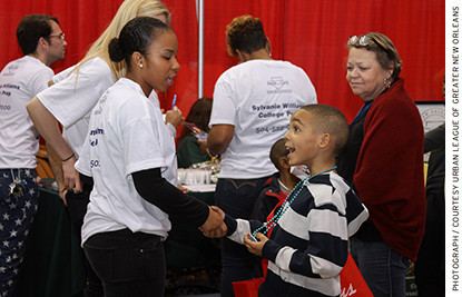 A potential student speaks with a Sylvanie Williams College Prep representa- tive at the Schools Expo hosted by the Urban League of Greater New Orleans