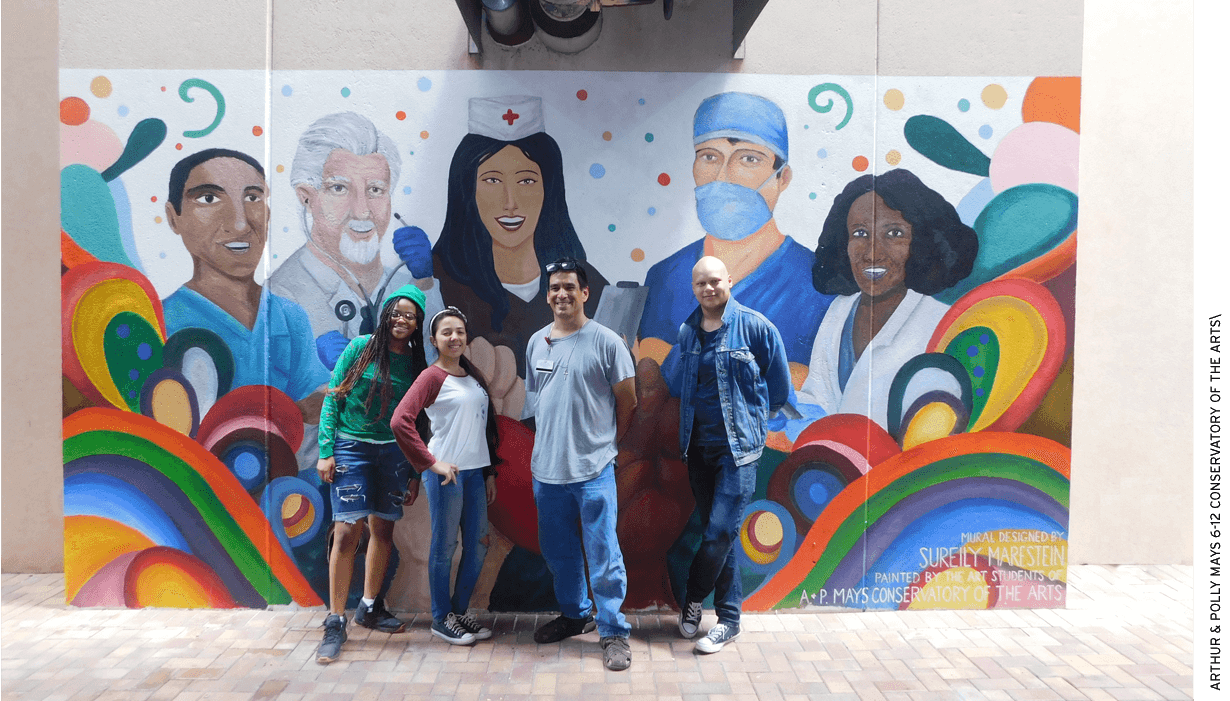 Art teacher Gerald Obregon and students from Arthur & Polly Mays Conservatory of the Arts, a public school, in front of a mural they painted on a wall at Kendall Regional Medical Center.