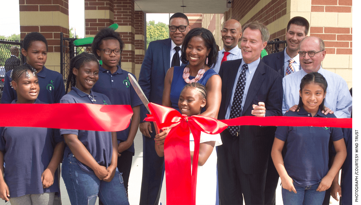 "Mariama Shaheed Carson (in blue dress), then Superintendent Lewis Ferebee, Indianapolis Mayor Joe Hogsett, and Brandon Brown cut a ribbon with students in July 2016 to celebrate the opening of Global Prep Academy. The school offers ""two-way immersion"" in English and Spanish."