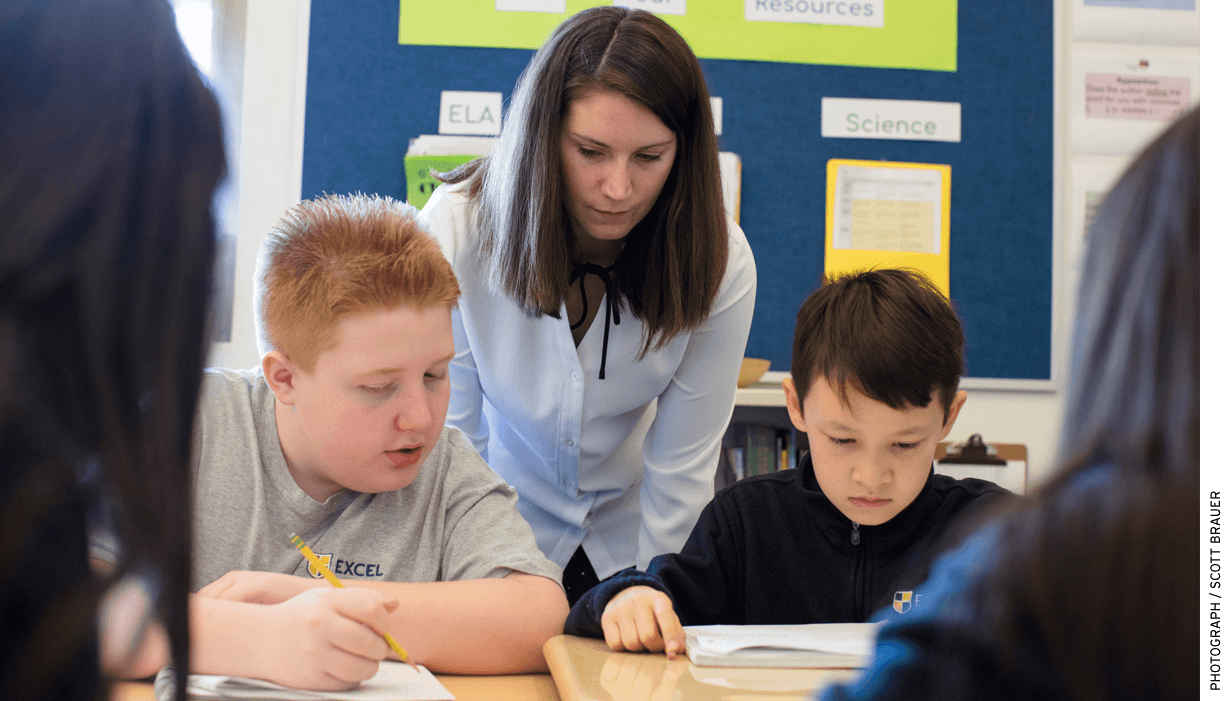 Samantha Butera, a 6th-grade learning specialist at Excel Academy East Boston, works with two students.