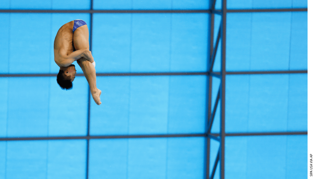 A diver in mid-flip heading down towards the pool.