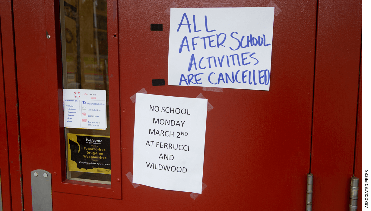 "A red door with posted signs that read ""All After School Activities Cancelled"" and ""No School Monday March 2nd"""