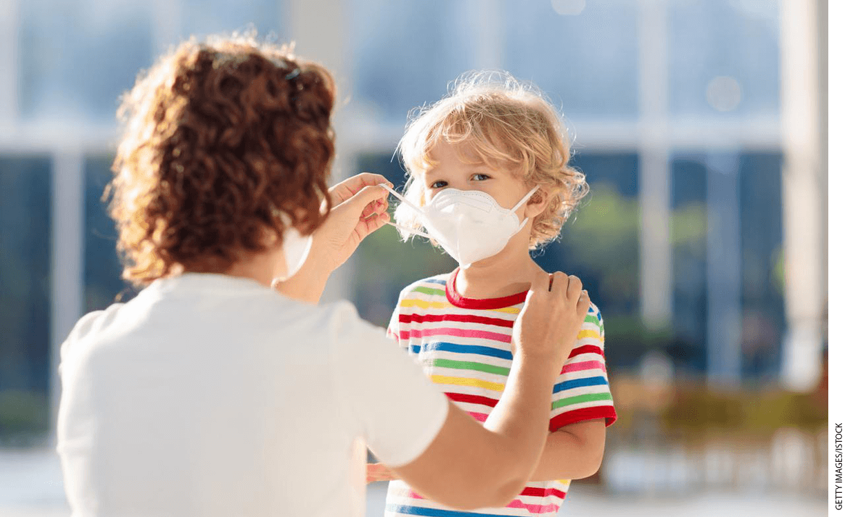 Adult fitting a surgical mask on a child