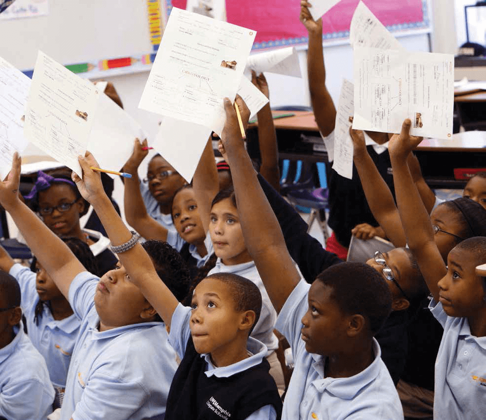 Students raising sheets of paper in the air in a classroom