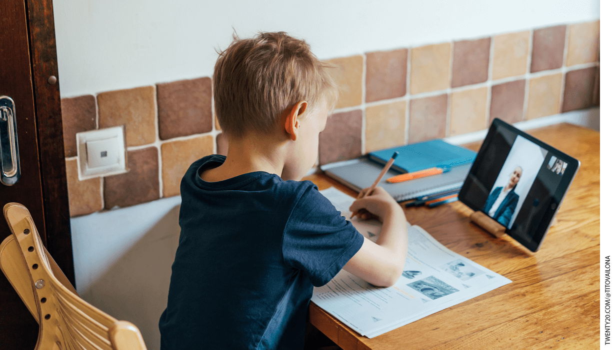A child sits at a table doing homework while watching a Zoom tutorial on an ipad.