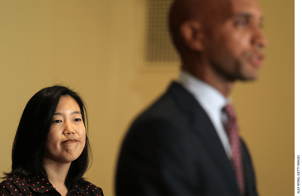 Chancellor Michelle Rhee (left) listens as Mayor Adrian Fenty speaks during a 2010 news conference at the end of her tenure.